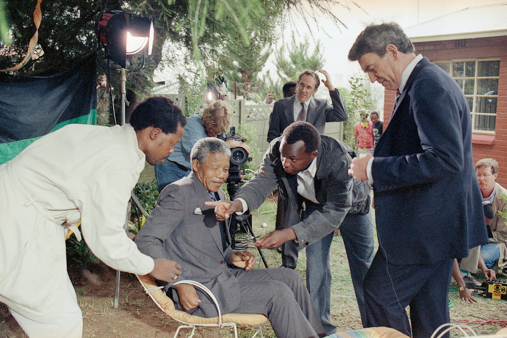 . Released ANC leader Nelson Mandela is wired for a television interview with CBS anchorman Dan Rather, right, Wednesday, Feb. 14, 1990 in the garden of his home in Soweto. Mandela spent most of his fourth day of freedom giving interview to the press. In the CBS interview Mandela spoke mainly about his experiences in jail. (AP Photo/John Parkin)