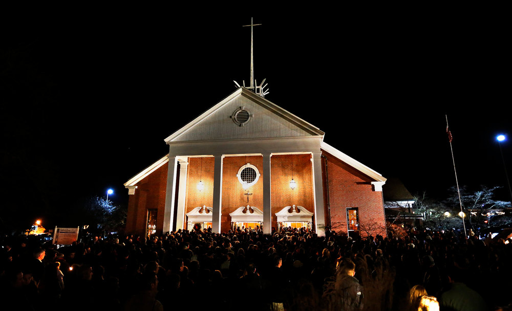 . People stand outside a vigil at the Saint Rose of Lima church in Newtown, Connecticut December 14, 2012. A heavily armed gunman opened fire on school children and staff at a Connecticut elementary school on Friday, killing at least 28 people, including 20 children, in the latest in a series of shooting rampages that have tormented the United States this year.  REUTERS/Shannon Stapleton