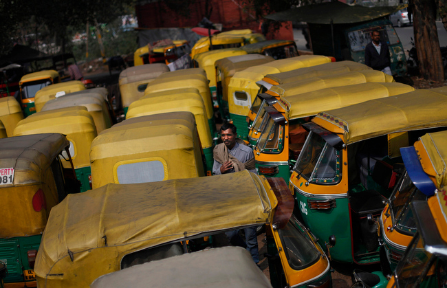 . An Indian auto-rickshaw driver stands among dozens of auto-rickshaws parked during a nationwide strike called by trade unions in New Delhi, India, Wednesday, Feb. 20, 2013. Sporadic violence has broken out in India at the beginning of a two-day strike by labor unions protesting rising prices and government policies to open the economy. Millions of bank and factory workers stayed away from work and public transport was shut down Wednesday after India\'s major trade unions called the countrywide strike. (AP Photo/Altaf Qadri)