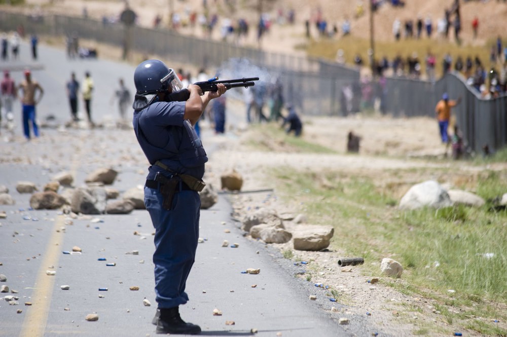 Description of . Members of the South African Police Services fire rubber bullets at striking farmworkers and other protestors during violent clashes, on January 10, 2012 in de Doorns, a small farming town about 140Km North of Cape Town. The farm workers have said that they they will not return to work on the fruit growing region's farms until they receive a daily wage of at least R150($17) per day, which is about double what they currently earn.AFP PHOTO / RODGER BOSCH/AFP/Getty Images
