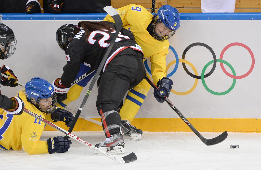 . Sweden\'s Josefine Holmgren (R) and Cecilia Ostberg (2ndL) vie with Japan\'s Ami Nakamura (C) during the Women\'s Ice Hockey Group B match Sweden vs Japan at the Shayba Arena during the Sochi Winter Olympics on February 9, 2014.  ANDREJ ISAKOVIC/AFP/Getty Images