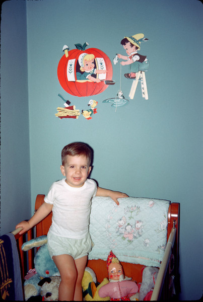 richard in crib with wall decorations.jpg