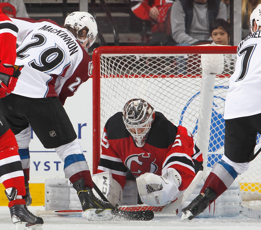 . Goalie Cory Schneider #35 of the New Jersey Devils stops a shot by Nathan MacKinnon #29 of the Colorado Avalanche during the second period of an NHL hockey game at Prudential Center on February 3, 2014 in Newark, New Jersey.  (Photo by Paul Bereswill/Getty Images)