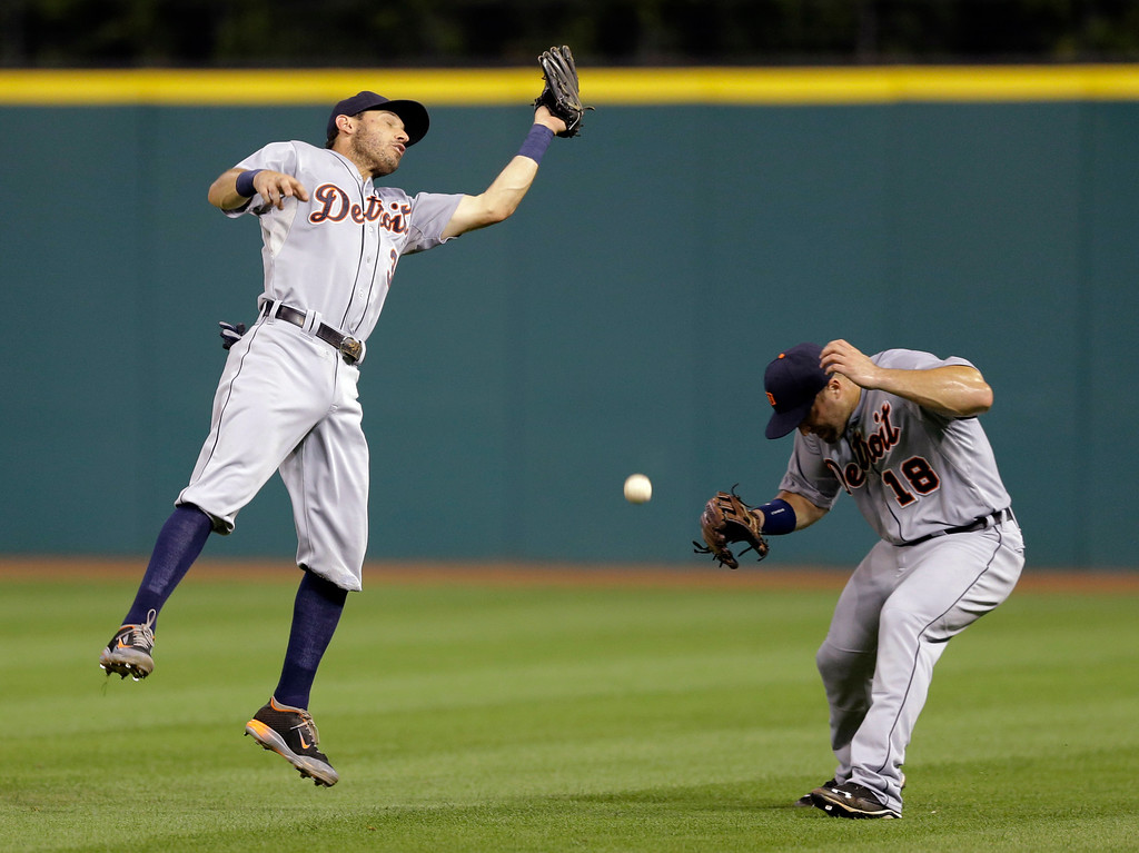 . Detroit Tigers\' Ian Kinsler, left, can\'t get to a ball hit by Cleveland Indians\' Carlos Santana in the fourth inning of a baseball game, Thursday, Sept. 4, 2014, in Cleveland. Kinsler was charged with an error. Tyler Collins, right, ducks. Santana was safe at first base. (AP Photo/Tony Dejak)