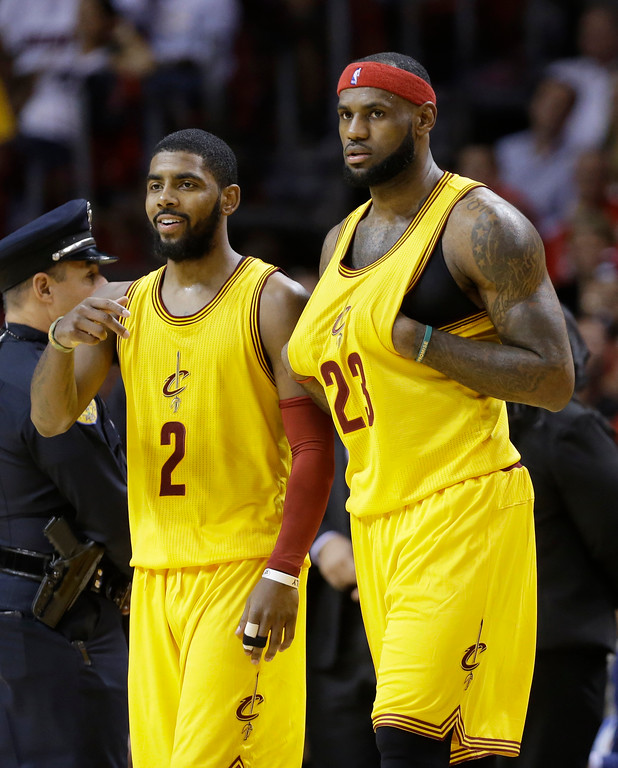 . Cleveland Cavaliers guard Kyrie Irving (2) stands with forward LeBron James (23) during the second half of an NBA basketball game against the Miami Heat, Thursday, Dec. 25, 2014, in Miami. The Heat defeated the Cavaliers 101-91. (AP Photo/Lynne Sladky)