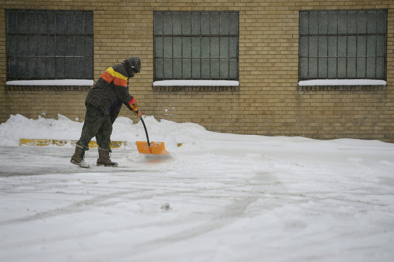 . Willie Edwards shovels snow in the 7-11 parking lot at University and Wesley in south Denver. Snow is expected to fall throughout the day. (Photo by AAron Ontiveroz/The Denver Post)