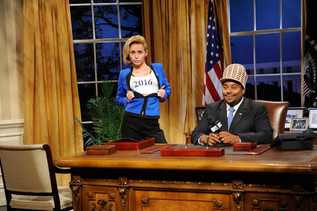 """. Guest host Miley Cyrus, left, and  Kenan Thompson in a scene from the late-night comedy series \""""Saturday Night Live,\"""" in New York on Oct. 5, 2013. (AP Photo/NBC, Dana Edelson)"""