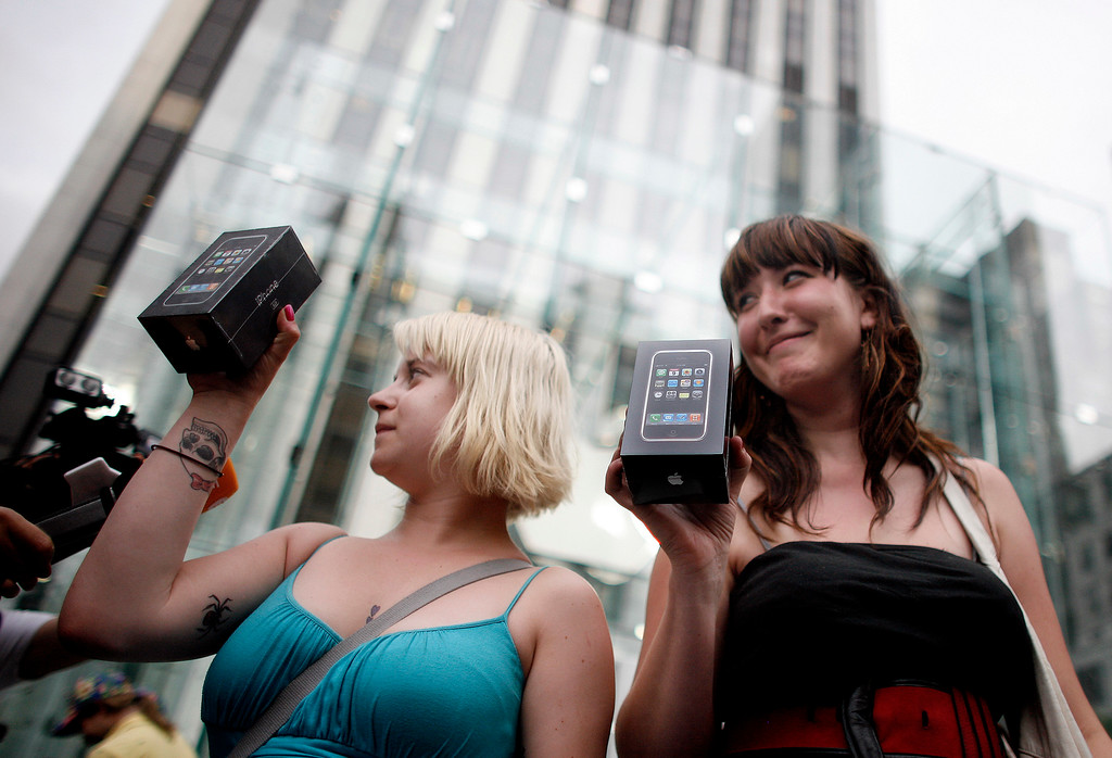 . Two women show off their new iPhones as they leave the Apple Store, Friday, June 29, 2007 in New York. Hundreds of people who lined up to be among the first to get their hands on Apple Inc.\'s coveted iPhone are now the braggarts and guinea pigs for the latest must-have, cutting-edge piece of techno-wizardry. (AP Photo/Jason DeCrow)