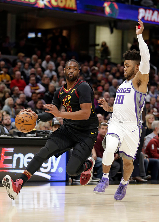 . Cleveland Cavaliers\' Dwyane Wade, left, drives past Sacramento Kings\' Frank Mason III in the first half of an NBA basketball game, Wednesday, Dec. 6, 2017, in Cleveland. (AP Photo/Tony Dejak)