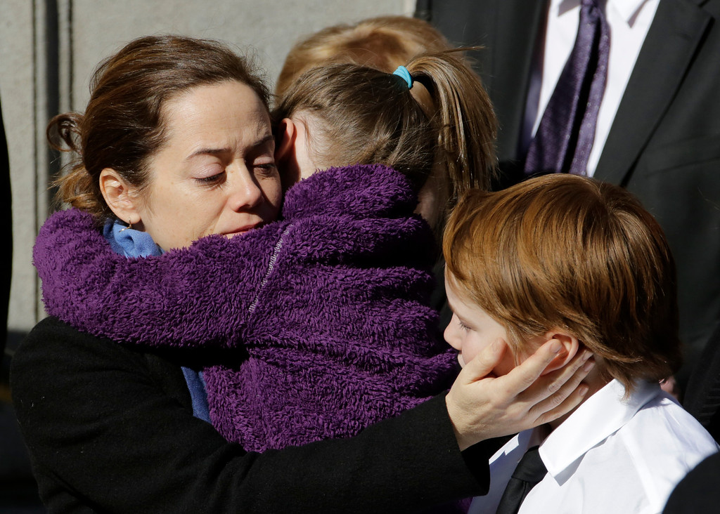 . Mimi O\'Donnell, estranged partner of actor Philip Seymour Hoffman, comforts two of their children, daughter Willa, and son Cooper as his casket arrives at the Church of St. Ignatius Loyola, Friday, Feb. 7, 2014 in New York. Hoffman, 46, was found dead Sunday of an apparent heroin overdose. (AP Photo/Mark Lennihan)