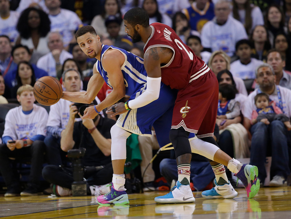 . Golden State Warriors\' Stephen Curry is guarded by Cleveland Cavaliers\' Kyrie Irving during the first half of an NBA basketball game Friday, Dec. 25, 2015, in Oakland, Calif. (AP Photo/Marcio Jose Sanchez)