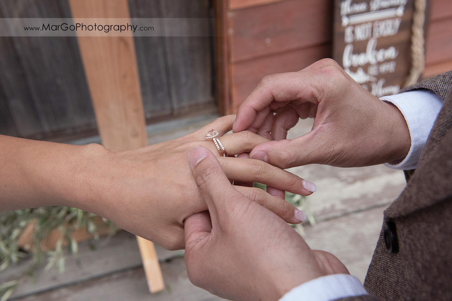 groom putting on wedding ring on bride's hand during wedding ceremony at Long Branch Saloon & Farms in Half Moon Bay