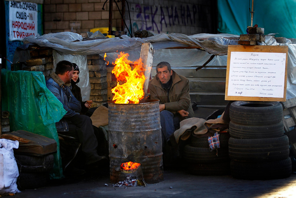 . Ukrainian veterans of Euro-maidan movement keep warm next to a makeshift fire while guarding one of the barricades they put up months ago, at the Independence Square in Kiev, Ukraine, 12 March 2014. The USA and European Union have threatened sanctions against Moscow over the military standoff in the strategic Crimean peninsula, and are urging Russia to pull back its forces in the region and allow in international observers and human rights monitors. Crimea, which has a majority ethnic Russian population, is strategically important to Russia as the home port of its Black Sea Fleet.  EPA/ROBERT GHEMENT