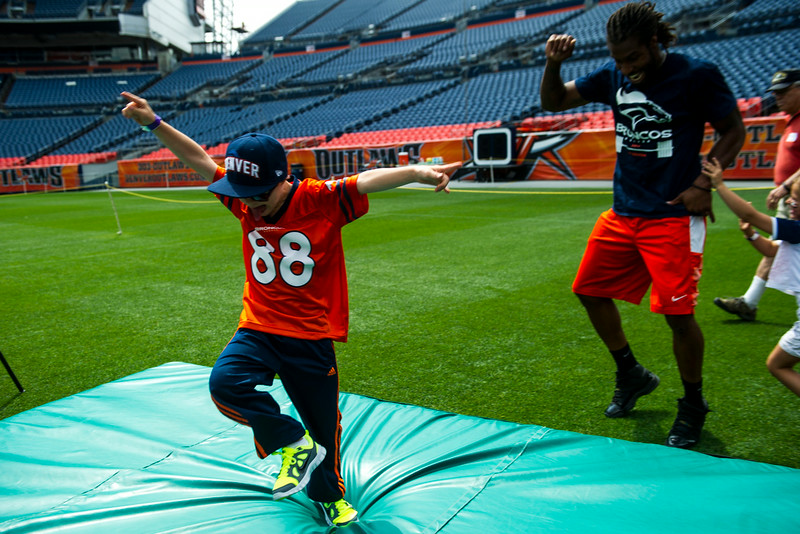 . Jaxson Schulte, 8, of Littleton does a touchdown dance with David Bruton #30 of the Denver Broncos during the National Sports Center for the Disabled\'s Denver Broncos Ability Clinic at Sports Authority Field at Mile High on Tuesday, July 08, 2014 in Denver, CO. (Photo by Kent Nishimura/The Denver Post)