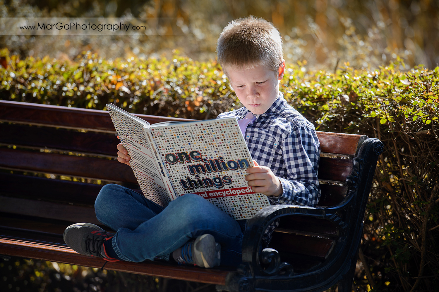 young boy reading book sitting on the bench at Mountain View Shoreline Lake Park