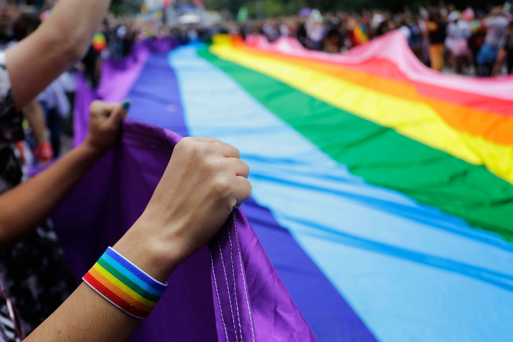 """. Revelers at the annual gay pride parade hold up a giant rainbow flag in Sao Paulo, Brazil, Sunday, June 3, 2018. This year the parade focused on the general elections scheduled for October, with the theme \""""Power for the LGBT. Our Vote, Our Voice.\"""" (AP Photo/Nelson Antoine)"""