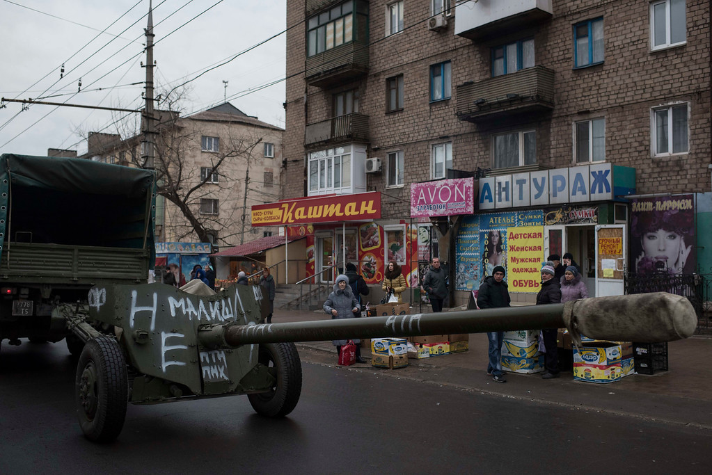 . Ukrainian weapons are towed by vehicles as heavy weapons are withdrawn in Mariupol, eastern Ukraine, Thursday, Feb. 26, 2015. In a long-awaited development, Ukrainian forces and separatist fighters both announced Thursday they are pulling back heavy weapons from the front line in eastern Ukraine. (AP Photo/Evgeniy Maloletka)