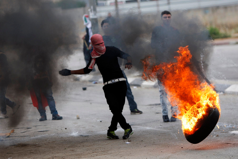 ". A masked Palestinian kicks a burning tire during clashes after a rally marking Nakba Day outside Ofer, an Israeli military prison near the West Bank town of Ramallah, Wednesday, May 15, 2013. Palestinians annually mark the ""nakba,\"" or \""catastrophe\"" - the term they use to describe their defeat and displacement in the war that followed Israel\'s founding in 1948. (AP Photo/Majdi Mohammed)"