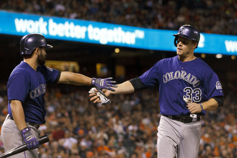 . Justin Morneau #33 of the Colorado Rockies is congratulated by Michael McKenry #8 after scoring a run against the San Francisco Giants during the fourth inning at AT&T Park on August 25, 2014 in San Francisco, California.  (Photo by Jason O. Watson/Getty Images)