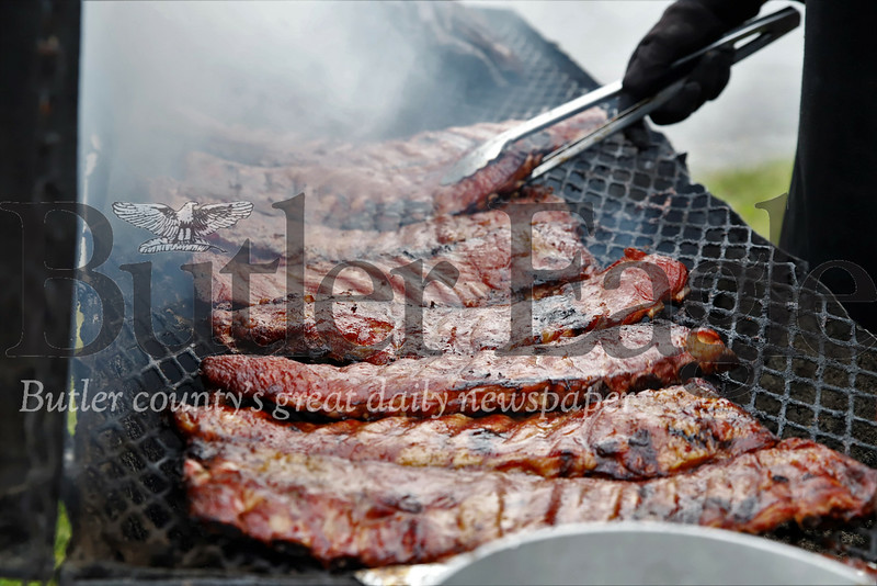 A server puts the finishing touches on a fresh order of ribs at the Butler Rib & Music Festival. Seb Foltz/ Butler Eagle
