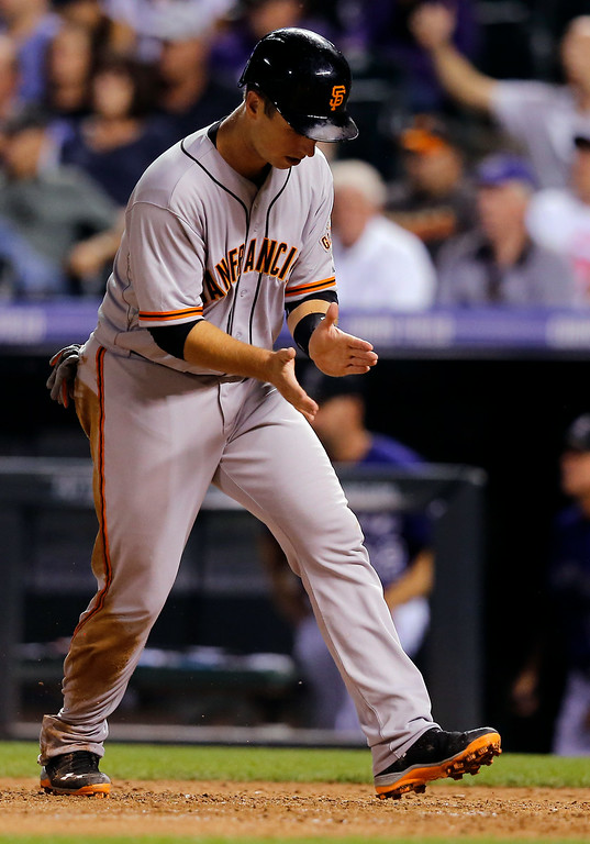 . San Francisco Giants\' Buster Posey claps after scoring against the Colorado Rockies  during the seventh inning of a baseball game Tuesday, Sept. 2, 2014, in Denver. (AP Photo/Jack Dempsey)