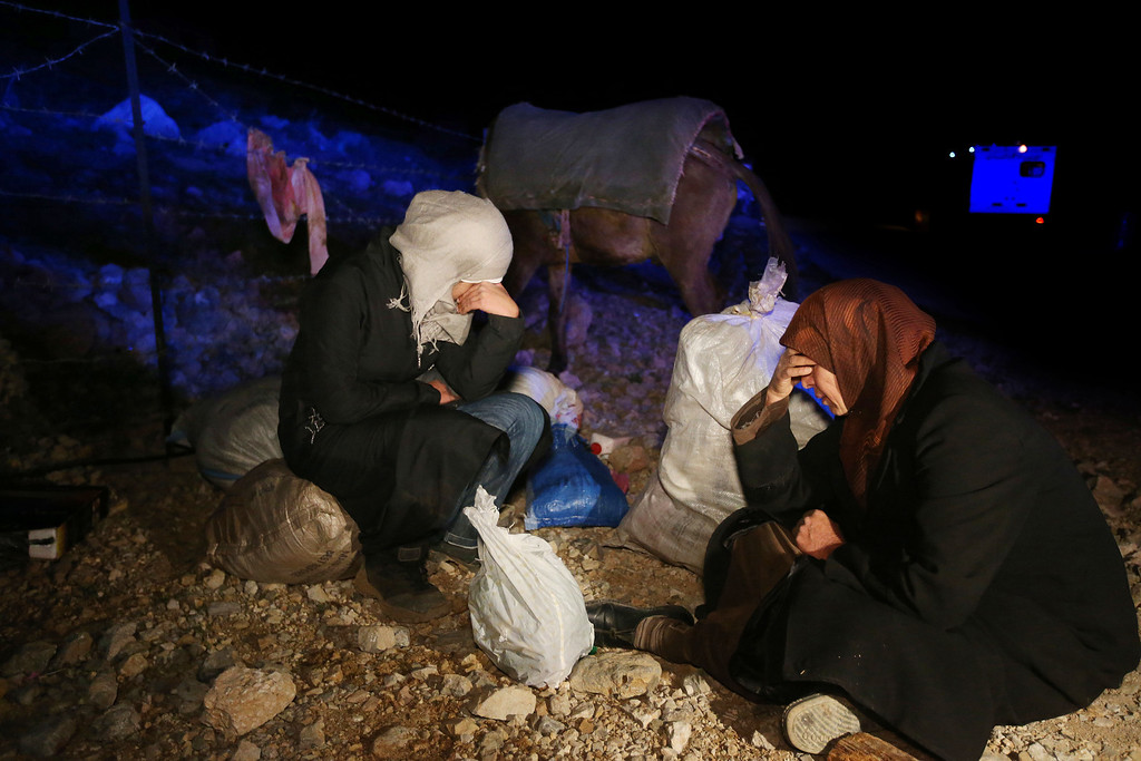 . In this picture taken early Sunday, April 20, 2014, Samira Asrawi 45, right, and her daughter Marwa, 19, left, sit on the ground weeping next to their belongings as they wait to be vetted by Lebanese soldiers at an army check point after descending from 2,814-meter (9,232-foot) high Mount Hermon (Jabal el-Sheikh) and reached the town of Chebaa in southeast Lebanon. They were part of a group of around a dozen Syrians desperate to flee their countryís bloody civil war who fled their home in the village of Beit Jinn, near the Israeli-occupied Golan Heights. They took part in a treacherous nighttime trek across the rugged frontier into neighboring Lebanon.(AP Photo/Hussein Malla)
