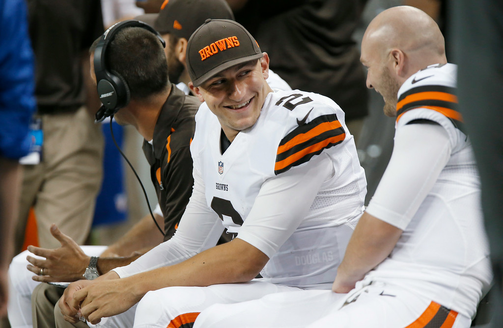 . Cleveland Browns quarterback Johnny Manziel (2) smiles on the bench against the Detroit Lions in the first half of a preseason NFL football game at Ford Field in Detroit, Saturday, Aug. 9, 2014.  (AP Photo/Duane Burleson)