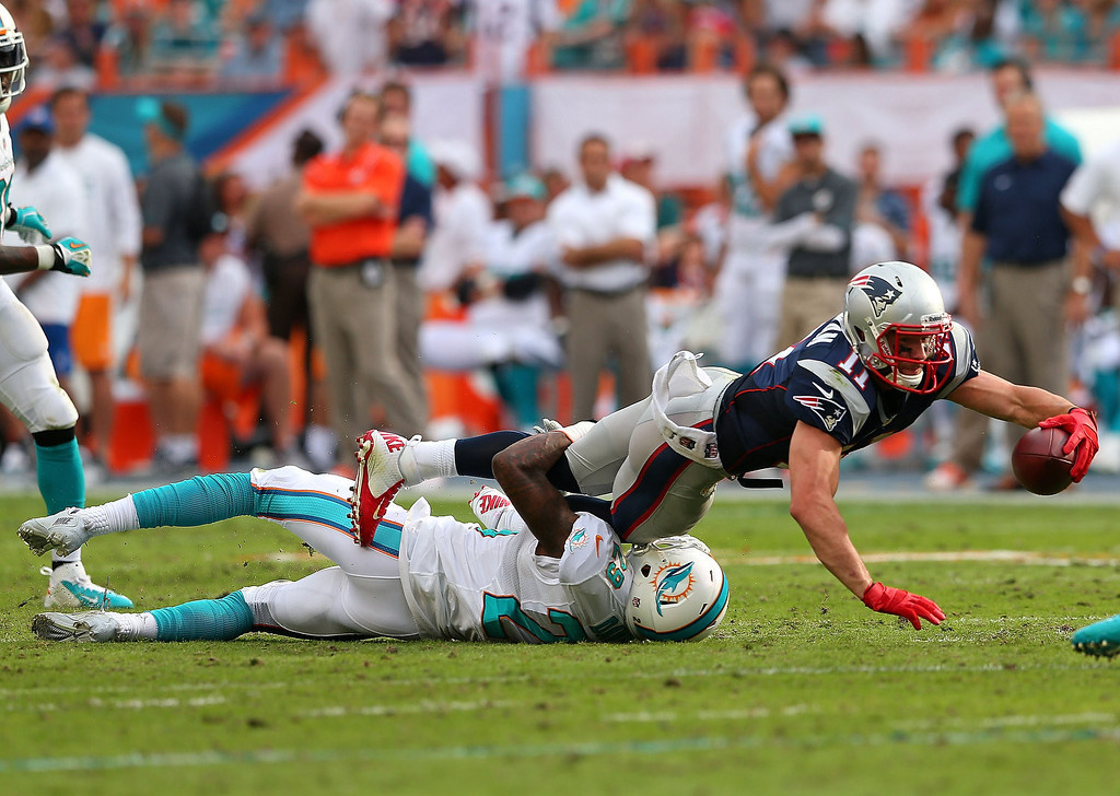 . Julian Edelman #11 of the New England Patriots is tackled by Nolan Carroll #28 of the Miami Dolphins during a game  at Sun Life Stadium on December 15, 2013 in Miami Gardens, Florida.  (Photo by Mike Ehrmann/Getty Images)