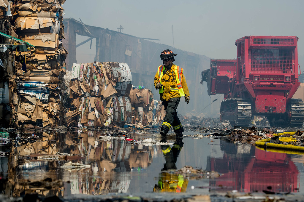. Firefighters mop-up a 5-alarm fire at a recycling center in the 14000 block of Marquardt Avenue in Santa Fe Springs on Friday morning, May 30, 2014. No injuries and the cause is under investigation. (Staff photo by Watchara Phomicinda/ Whittier Daily News)