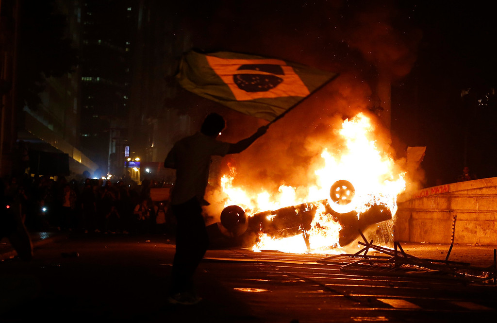 . A demonstrator waves a Brazilian flag by a burning a car in downtown Rio de Janeiro June 17, 2013.Tens of thousands of demonstrators marched through the streets of Brazil\'s biggest cities on Monday in a growing protest that is tapping into widespread anger at poor public services, police violence and government corruption.    REUTERS/Sergio Moraes