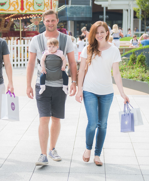 Izmi_Baby_Carrier_Mid_Grey_Lifestyle_Front_Facing_Carry_Mum_And_Dad_Shopping.jpg