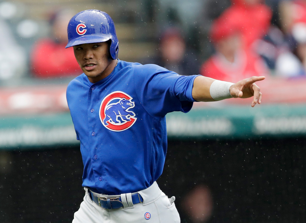 . Chicago Cubs\' Addison Russell points to Ian Happ after Happ hit an RBI-single off Cleveland Indians starting pitcher Josh Tomlin in the second inning of a baseball game, Tuesday, April 24, 2018, in Cleveland. Russell scored on the play. (AP Photo/Tony Dejak)
