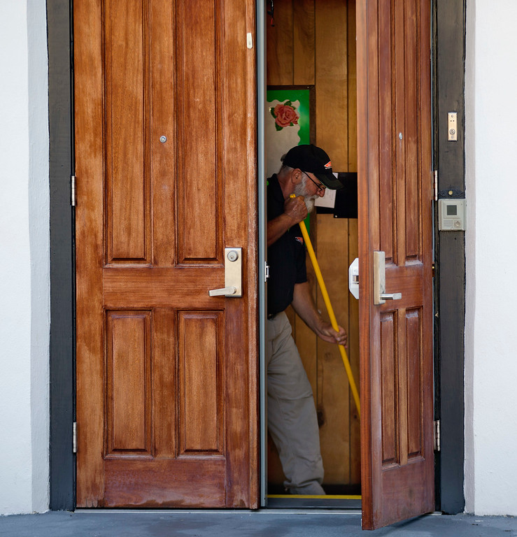 . A member of a cleaning crew mops a floor inside the Emanuel AME Church where nine people at the historic black church were killed Wednesday in a shooting in Charleston, S.C., Saturday, June 20, 2015. (AP Photo/David Goldman)