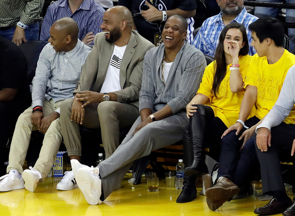 . Rapper Jay-Z, center, watches Game 1 of basketball\'s NBA Finals between the Golden State Warriors and the Cleveland Cavaliers Thursday, June 1, 2017, in Oakland, Calif. (AP Photo/Marcio Jose Sanchez)