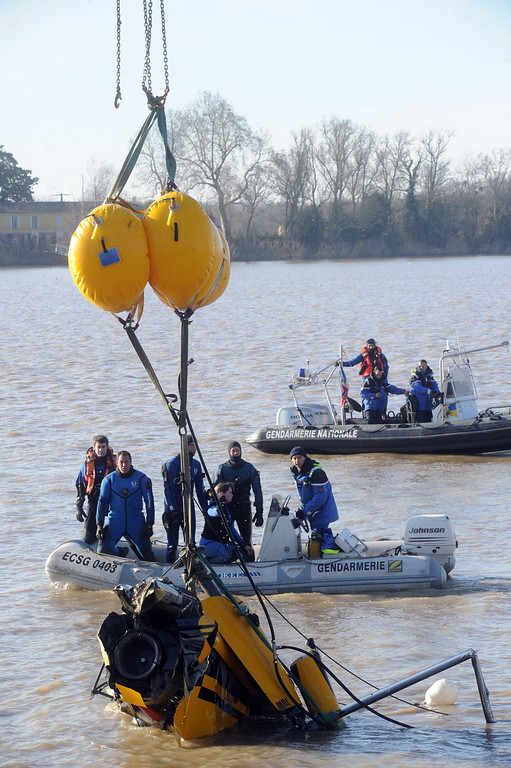 . Gendarmes take part in an operation to lift a helicopter from the Dordogne river bed for clues into a crash that is thought to have killed a Chinese tycoon and a French winemaker.AFP PHOTO / MEHDI FEDOUACH