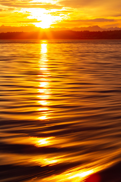 Golden sunrise across a small waves of Puget Sound