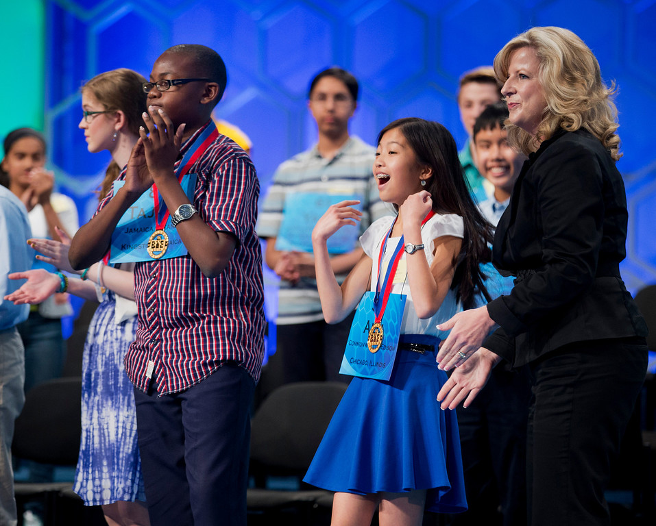 . From left,  Mary Horton, 13, of West Melbourne, Fla., Tajaun Gibbison, 13, of Mandeville, Jamaica, and Alia Abiad, 14, of Western Springs, Ill., celebrate, after receiving their medals from Paige Kimble, right, executive director of the Scripps National Spelling Bee, and making it to the finals of the Scripps National Spelling Bee, Thursday, May 29, 2014, at National Harbor in Oxon Hill, Md.  (AP Photo/Manuel Balce Ceneta)