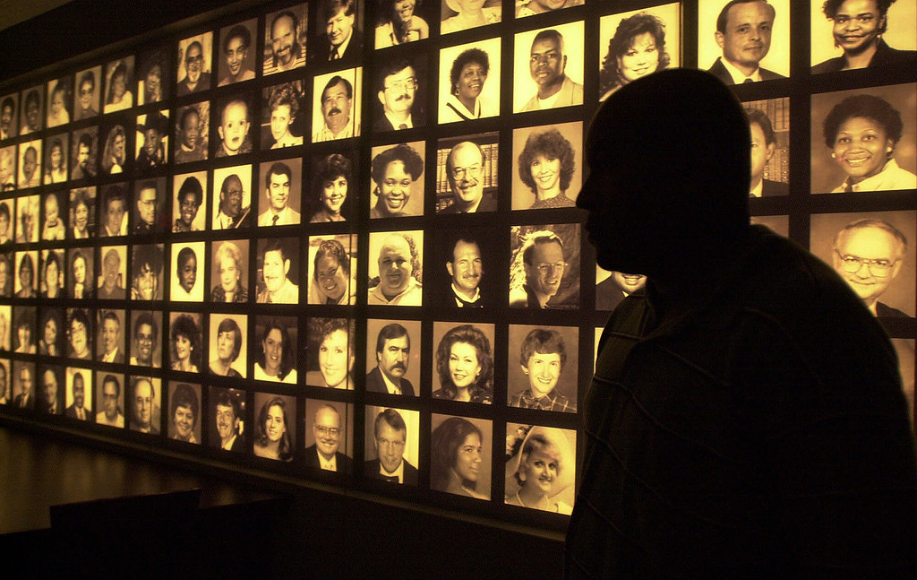 . FILE - In this June 8, 2001 file photo, Terry Foster of Detroit stands in front of a wall of photographs at the Oklahoma City National Memorial Center. The photos are of the 168 victims who died in the Oklahoma City bombing. (AP Photo/Laura Rauch)