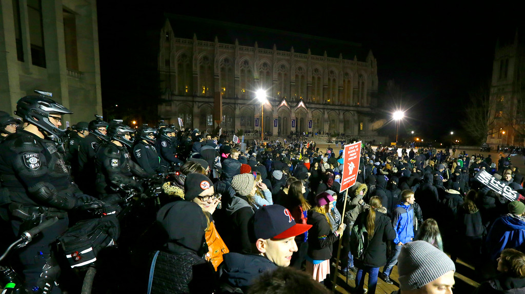 . Protesters and police gather in front of Kane Hall on the University of Washington campus where far-right commentator Milo Yiannopoulos was giving a speech, Friday, Jan. 20, 2017, in Seattle. (AP Photo/Ted S. Warren)
