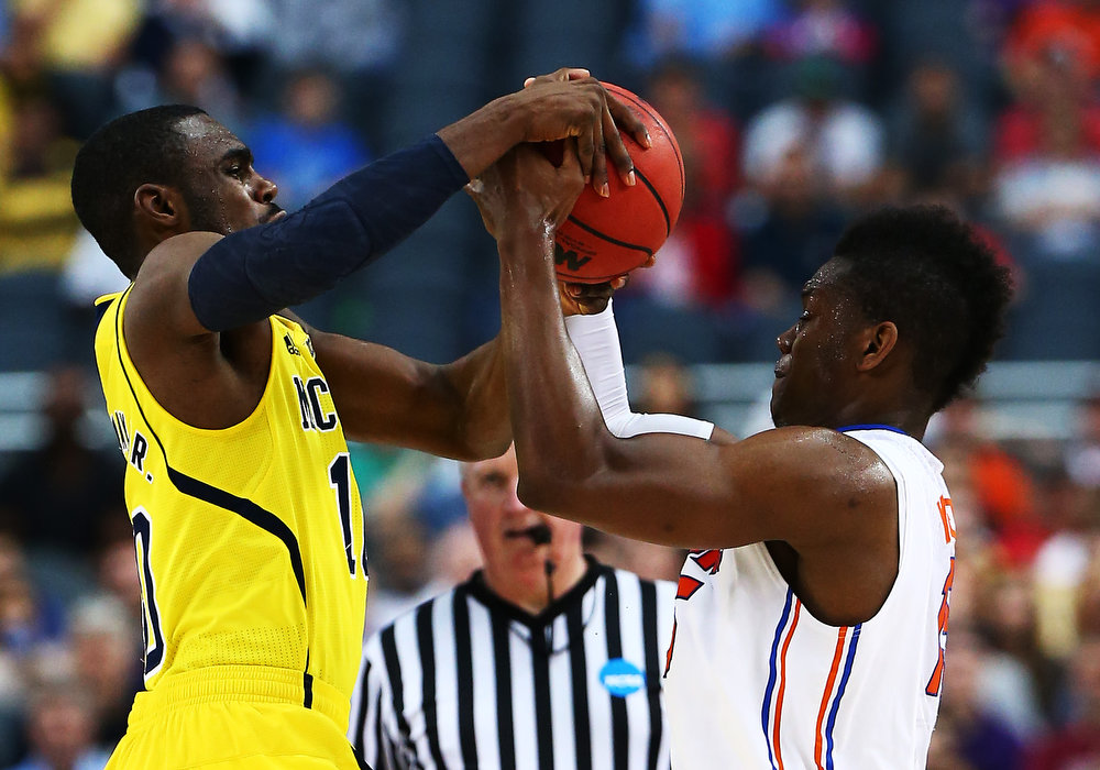 Description of . Tim Hardaway Jr. #10 of the Michigan Wolverines and Will Yeguete #15 of the Florida Gators vie for posession in the first half during the South Regional Round Final of the 2013 NCAA Men\'s Basketball Tournament at Dallas Cowboys Stadium on March 31, 2013 in Arlington, Texas.  (Photo by Tom Pennington/Getty Images)