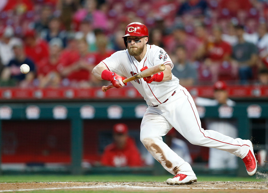 . Cincinnati Reds\' Tucker Barnhart bunts for a single off Cleveland Indians starting pitcher Shane Bieber during the third inning of a baseball game Wednesday, Aug. 15, 2018, in Cincinnati. Barnhart wound up at third after a throwing error on the play. (AP Photo/Gary Landers)