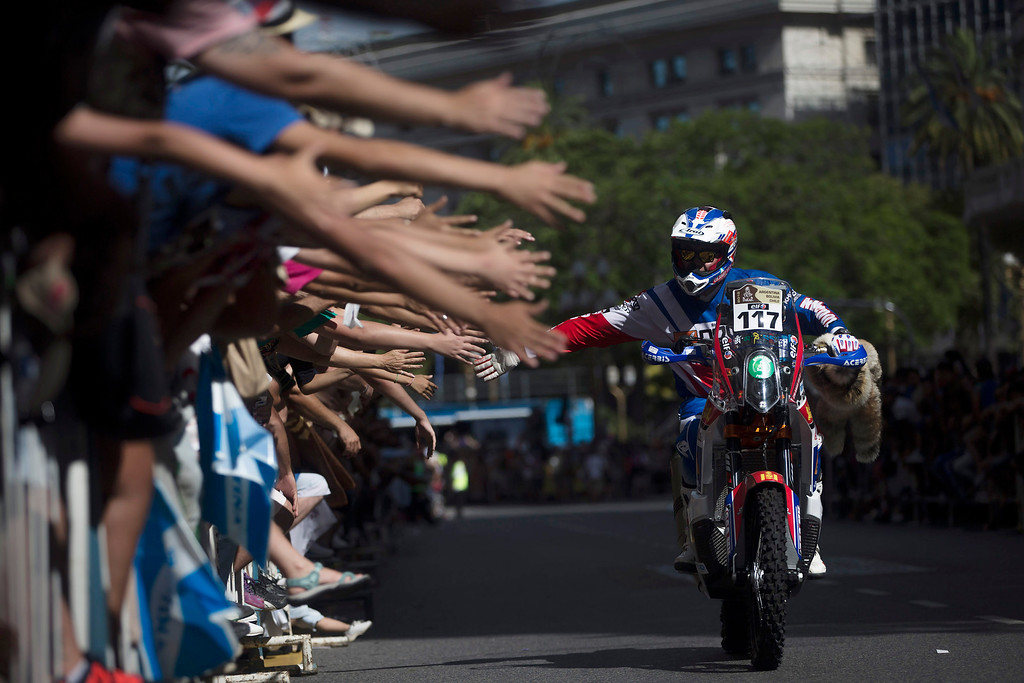 . KTM rider Anar Chinbataar of Mongolia greets spectators as he arrives for the symbolic start of the Dakar Rally 2015 in Buenos Aires, Argentina, Saturday, Jan. 3, 2015. The race will start on Jan. 4 and finish on Jan. 17, from Buenos Aires, passing through Bolivia and Chile and returning to Argentina. (AP Photo/Felipe Dana)
