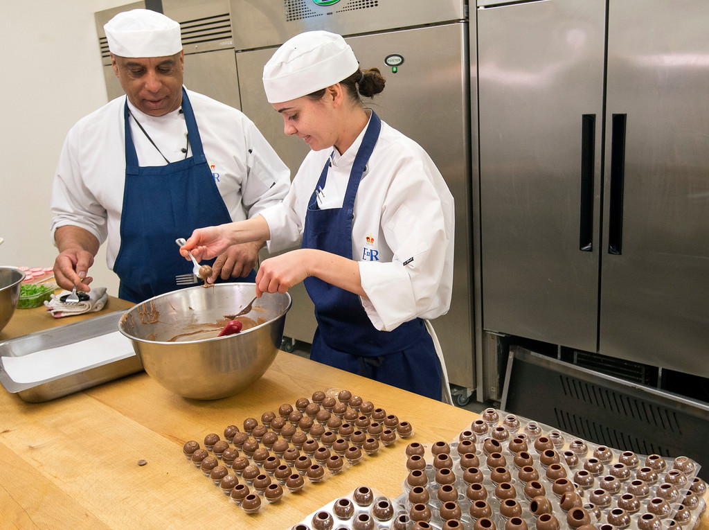 . In this photo taken on Thursday May 10, 2018, pastry chef Selwyn Stoby, left, and chef de partie Victoria Scupham work in the royal kitchen, as preparations are underway for the reception banquet after the wedding of Prince Harry and Meghan Markle on Saturday, May 19, in Windsor Castle, England. (David Parker/Pool Photo via AP)