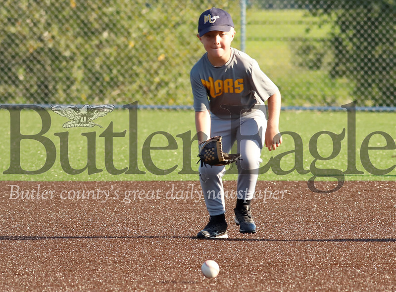 Landyn Moore of the 6-8 year-old Mars Pirates bears down on a ground ball at shortstop against the Mars Brewers Monday Night at the little league fields in Mars. Seb Foltz/Butler Eagle