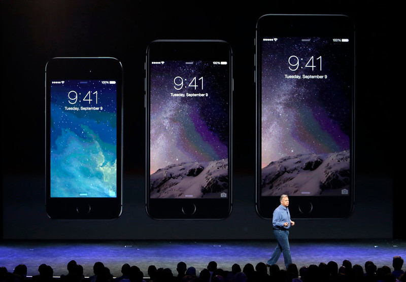 . Phil Schiller, Apple\'s senior vice president of worldwide product marketing, discusses the new iPhone 6, center, and iPhone 6 plus, right, on Tuesday, Sept. 9, 2014, in Cupertino, Calif. (AP Photo/Marcio Jose Sanchez)