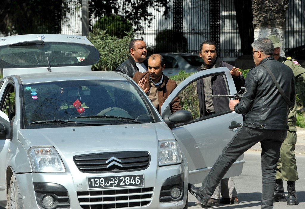 . Armed Tunisian policemen in plainclothes stop a vehicle as security forces secure the area after gunmen attacked Tunis\' famed Bardo Museum on March 18, 2015. At least seven foreigners and a Tunisian were killed in an attack by two men armed with assault rifles on the museum, the interior ministry said. AFP PHOTO / FETHI  BELAID/AFP/Getty Images