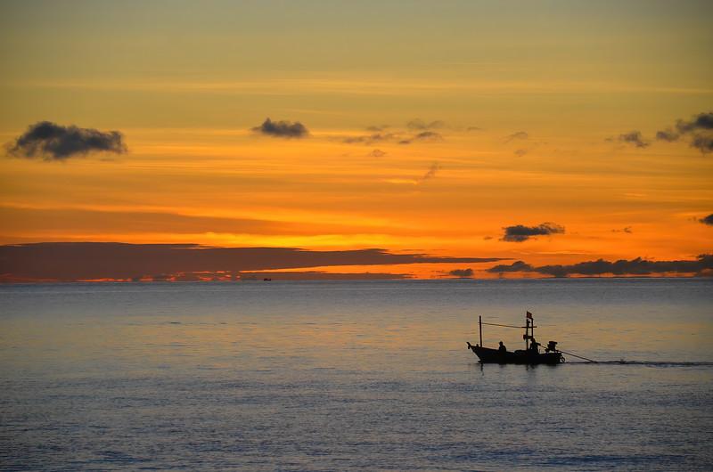 Colourful orange Cirrostratus cloudy tropical nautical sunrise seascape with fishing boat silhouette. Thailand.