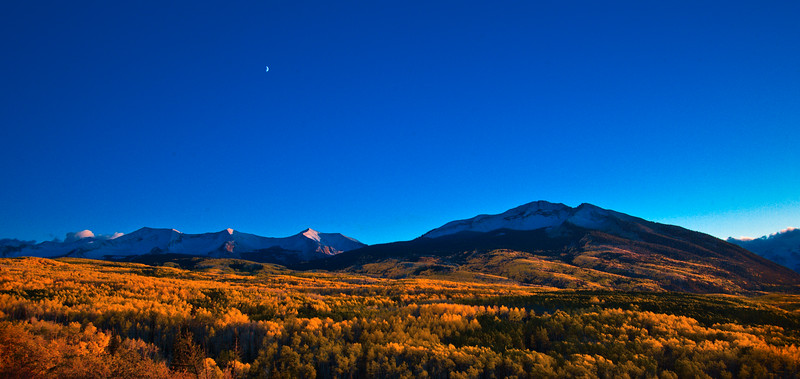Fall sunset and rising crescent moon over the West Elk Mountains from Kebler Pass between Crested Butte and Paonia, Colorado.