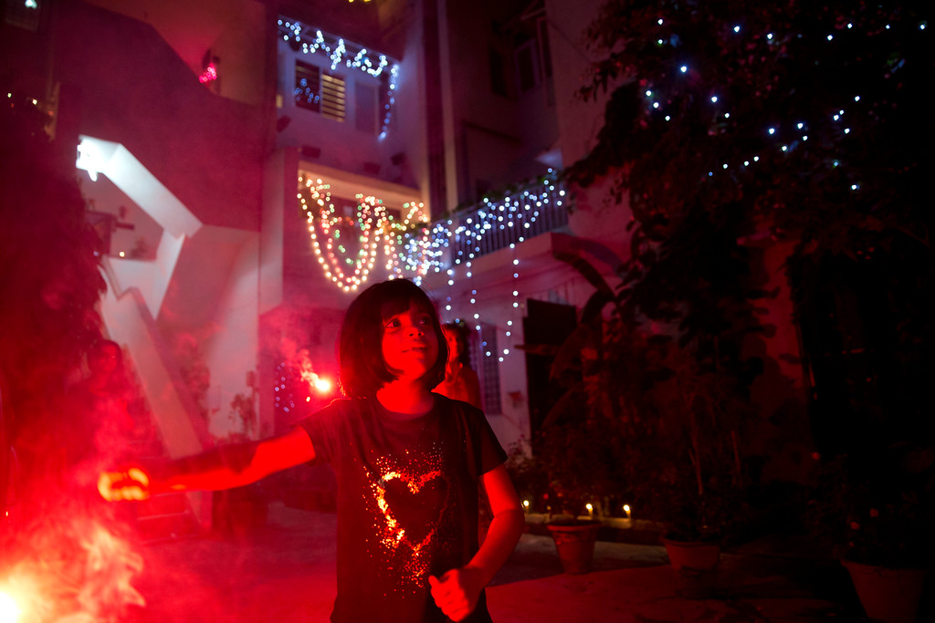 . An Indian girl plays with firecrackers during Diwali festival in New Delhi, India, Thursday, Oct. 19, 2017. Worried especially by the impact on the health of children, the Supreme Court this year banned the sale of firecrackers, that is usually in huge demand across the country as the evening sky is lit up by the festivities, in the Indian capital and neighboring areas to prevent a toxic haze after the Diwali nights that has residents hiding indoors. (AP Photo/Manish Swarup)