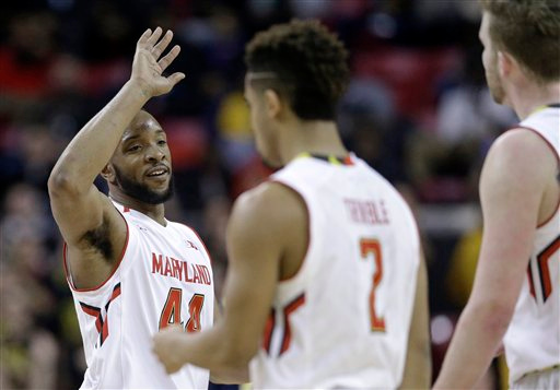 . Maryland guard/forward Dez Wells, left, high-fives teammates Melo Trimble (2) and Evan Smotrycz in the final moments of an NCAA college basketball game against Michigan, Saturday, Feb. 28, 2015, in College Park, Md. (AP Photo/Patrick Semansky)